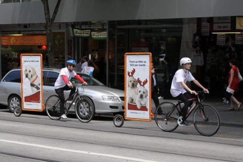 Cyclists towing advertisements behind their bikes