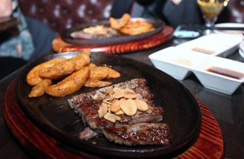 AAA Beef Filet Steak served on a hot stone plate with fresh garlic, soy onion sauce and a side of potato wedges sprinkled with shichimi spices, complimented by a house blue cheese sauce