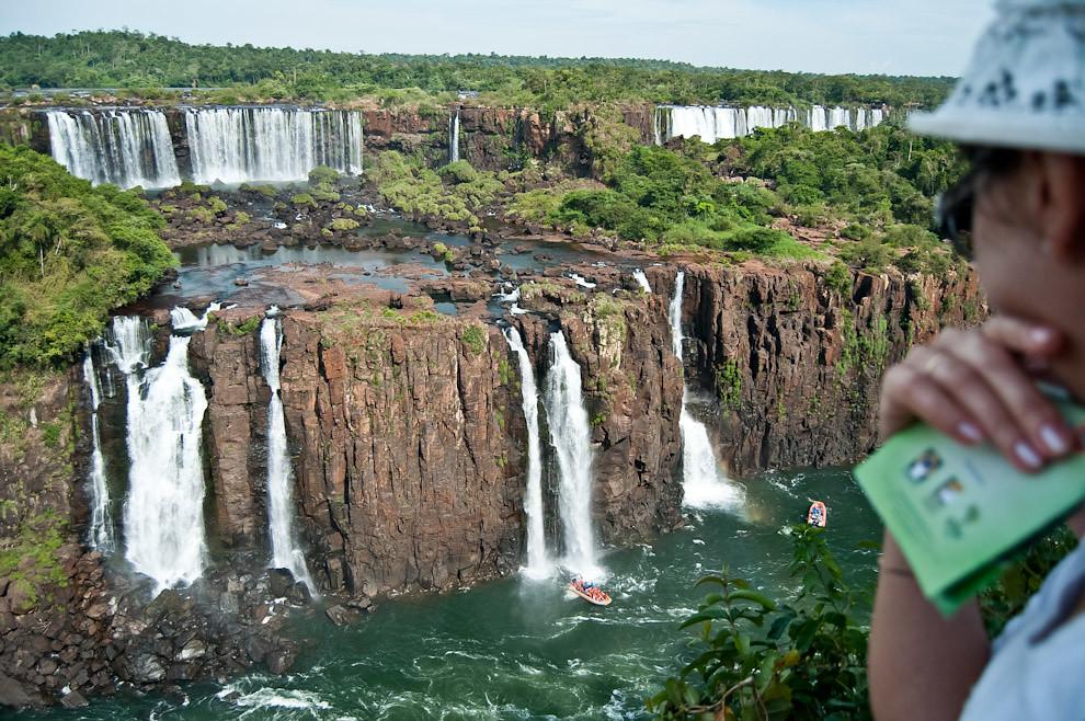 Una mujer observa como los turistas se divierten bajo las aguas de las cataratas, cuando el piloto de la lancha los acerca a la cascada se mojan totalmente mientras lanzan gritos de vértigo y emoción. (Elton Núñez)