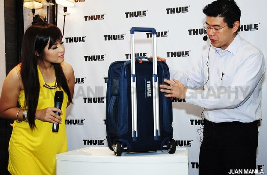 Melvin Sua, Managing Director, Jake Bros. Inc., local distributor of THULE shows the propriety V-tubing  (telescoping handles) of the Crossover Collection rolling luggage as MYX VJ AI Dela Cruz, looks on.