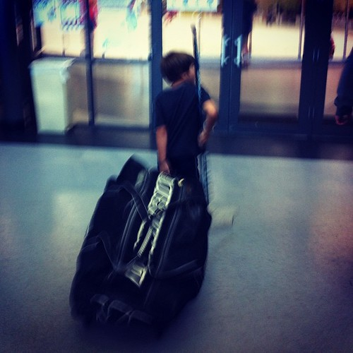 One kid, one huge bag of hockey gear.