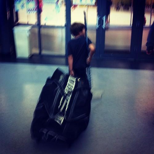 One kid, one huge bag of hockey gear.