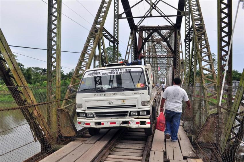 Puente que une Costa Rica con Panamá sobre un Río y por el que circulan personas, caminiones y algún que otro tren, el suelo es de tablones de madera con huecos donde se ve el río.
