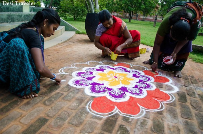 a team of women making floral rangoli design in Pondicherry India