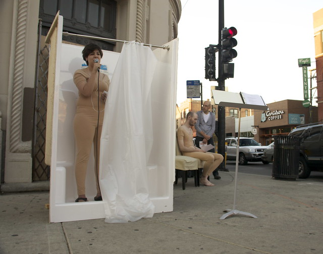 This is a picture of a woman in a tan bodysuit singing in a temporary shower stall outside of 1601 North Milwaukee while a man in a tan body suit sits on a couch and another man looks on.