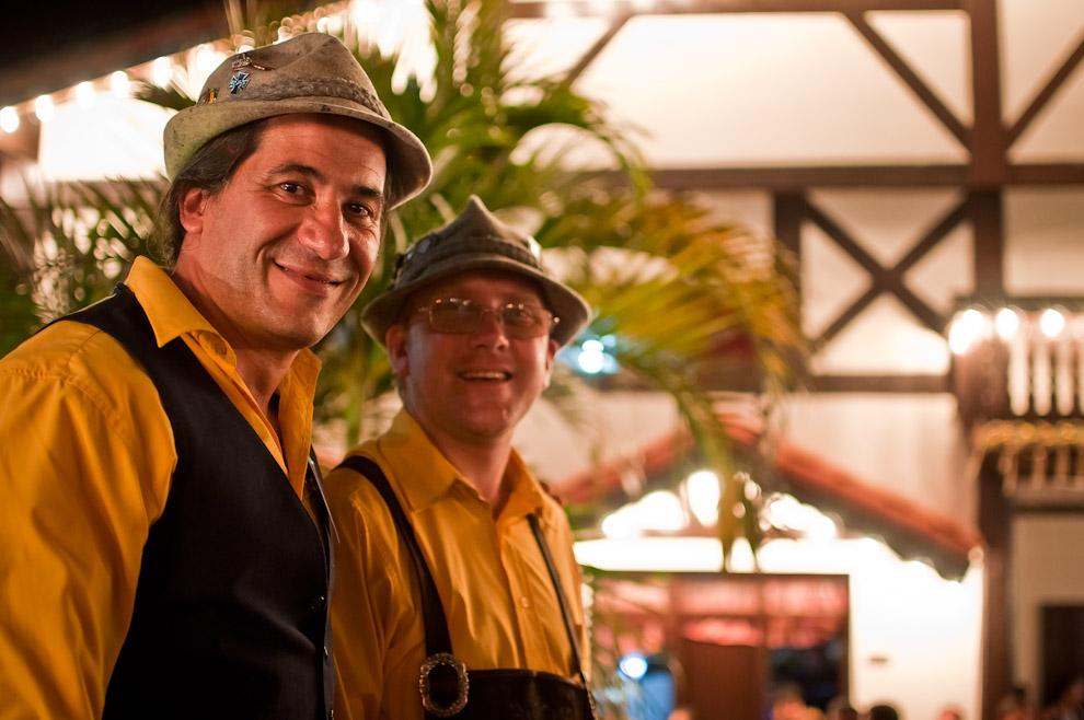 """Dos integrantes del conjunto musical """"Die Bier Musikanten"""", vestidos con el atuendo típico alemán, disfrutan y conversan frente al Club Alemán de Colonia Obligado mientras seguía la fiesta al son de la música de otras orquestas. (Elton Núñez)"""
