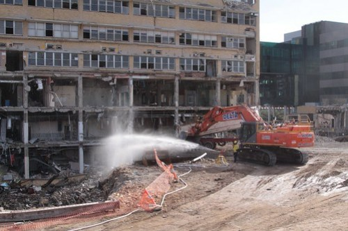 Spraying water over the rubble to control the dust