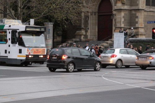 Cars delays trams as the queue through the intersection of Swanston and Flinders Streets