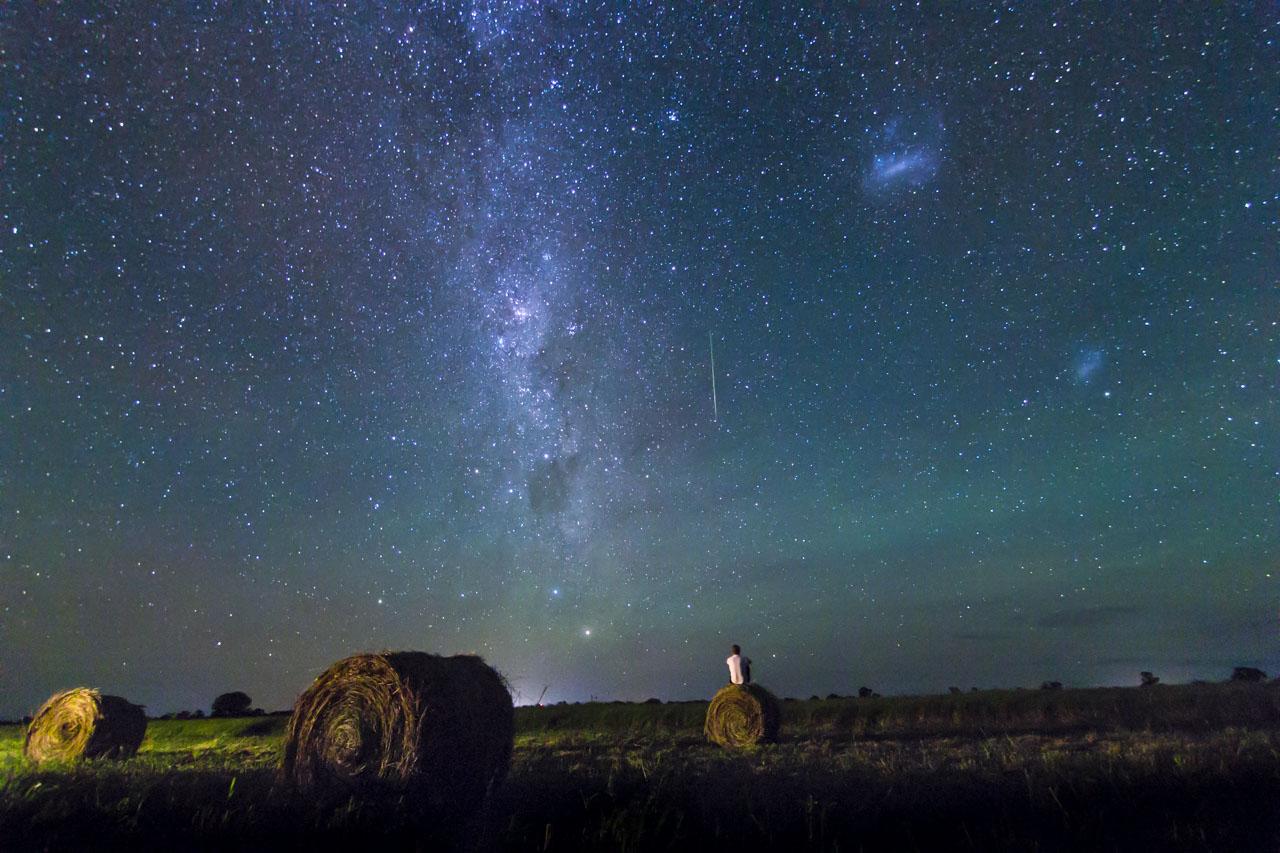 Una estrella fugaz recorre el cielo, con el centro de la vía láctea al costado, mientras observamos la grandeza del universo.