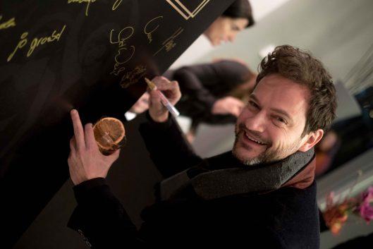Schauspieler Nicolai Tegeler verewigt sich im Hotel am Steinplatz (Credit: Henriette Becht)