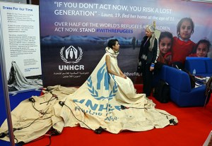"Project ambassador of ""Dress For Our Time"" Louise Owen models a UN tent from the Zaatari camp in Jordan that has been converted into a dress by fashion academic Helen Storey (R) at the Dubai Humanitarian Aid and Development conference and Exhibition in Dubai on March 22, 2017. / AFP PHOTO / NEZAR BALOUT"