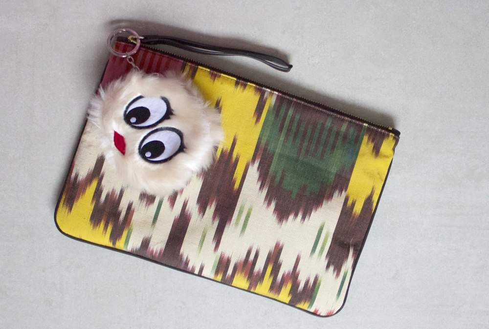 jaunt clutch bag with fur face bag charm