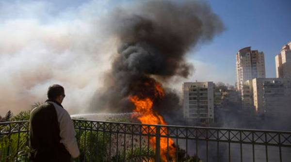 A man watches wildfires in Haifa, Israel, Thursday, Nov. 24, 2016. Israeli police have arrested four Palestinians in connection with one of several large fires that damaged homes and prompted the evacuation of thousands of people in the past few days. Police are investigating the causes, including possible arson. Windy and hot weather have helped fan the flames. The blazes started three days ago near Jerusalem and in the north. Hundreds of homes were damaged. Russia, Italy and other countries are assisting the Israeli firefighters.(AP Photo/Ariel Schalit)