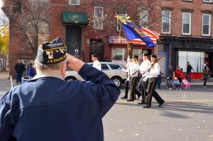 A veteran salutes while watching the Albany, N.Y. Veterans Day parade.
