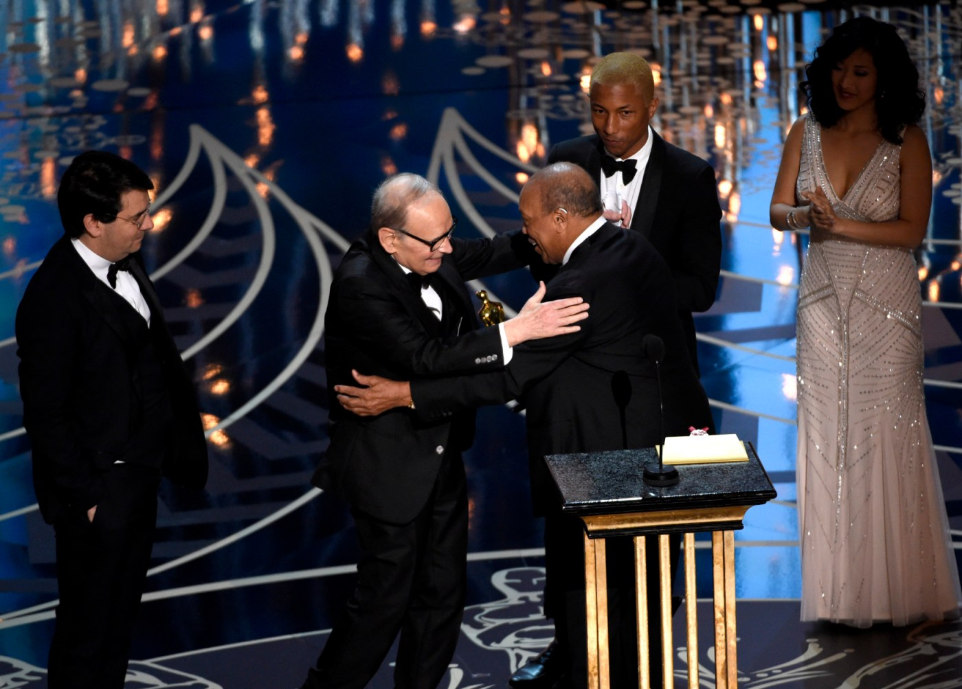 "Quincy Jones, center, and Pharell Williams, right, present Ennio Morricone with the award for best original score for ""The Hateful Eight"" at the Oscars on Sunday, Feb. 28, 2016, at the Dolby Theatre in Los Angeles. (Photo by Chris Pizzello/Invision/AP)"