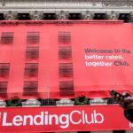 FILE PHOTO --  A woman looks at her phone as she passes by a Lending Club banner on the facade of the the New York Stock Exchange December 11, 2014.   REUTERS/Brendan McDermid/File Photo
