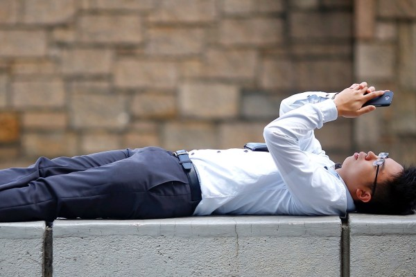 A businessman relaxes on a barrier between closed roads in the part of Hong Kong's financial central district pro-democracy protesters are occupying October 31, 2014. The former British colony of Hong Kong, which returned to Chinese rule in 1997, has witnessed a month of protests calling on the Beijing-backed government to keep its promise of introducing universal suffrage. The protests have for the most part been peaceful, with occasional clashes between the student-led protesters and Beijing supporters seeking to move them from the streets.  REUTERS/Damir Sagolj (CHINA - Tags: POLITICS CIVIL UNREST BUSINESS) - RTR4CA0U