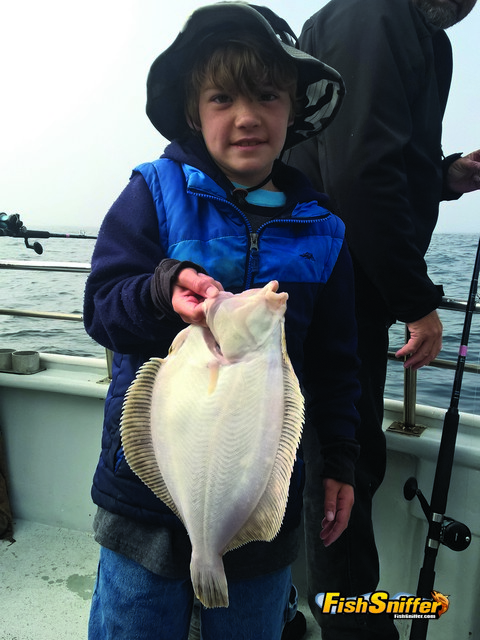 Jacob Ward shows off a handsome rocksole he caught while fishing about the Sea Wolf during the recent Cub Scout saltwater adventure.