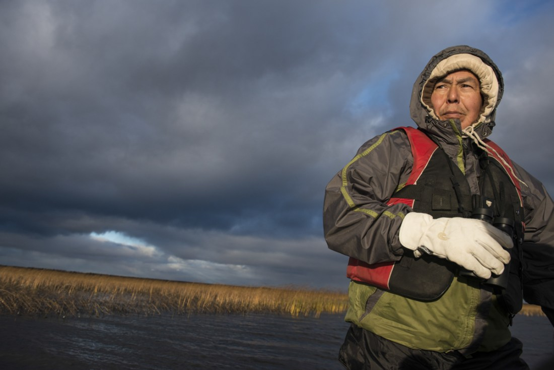 "Lloyd Chicot navigates his boat through Tathlina Lake. ""There's been a lot of development in these parts the last 50 years or so. If you fly over, you can seismic lines all over the place,"" he says. ""It never used to be like that - there are less moose in the area now and the summer's are longer. Development and climate change is impacting our way of life."""