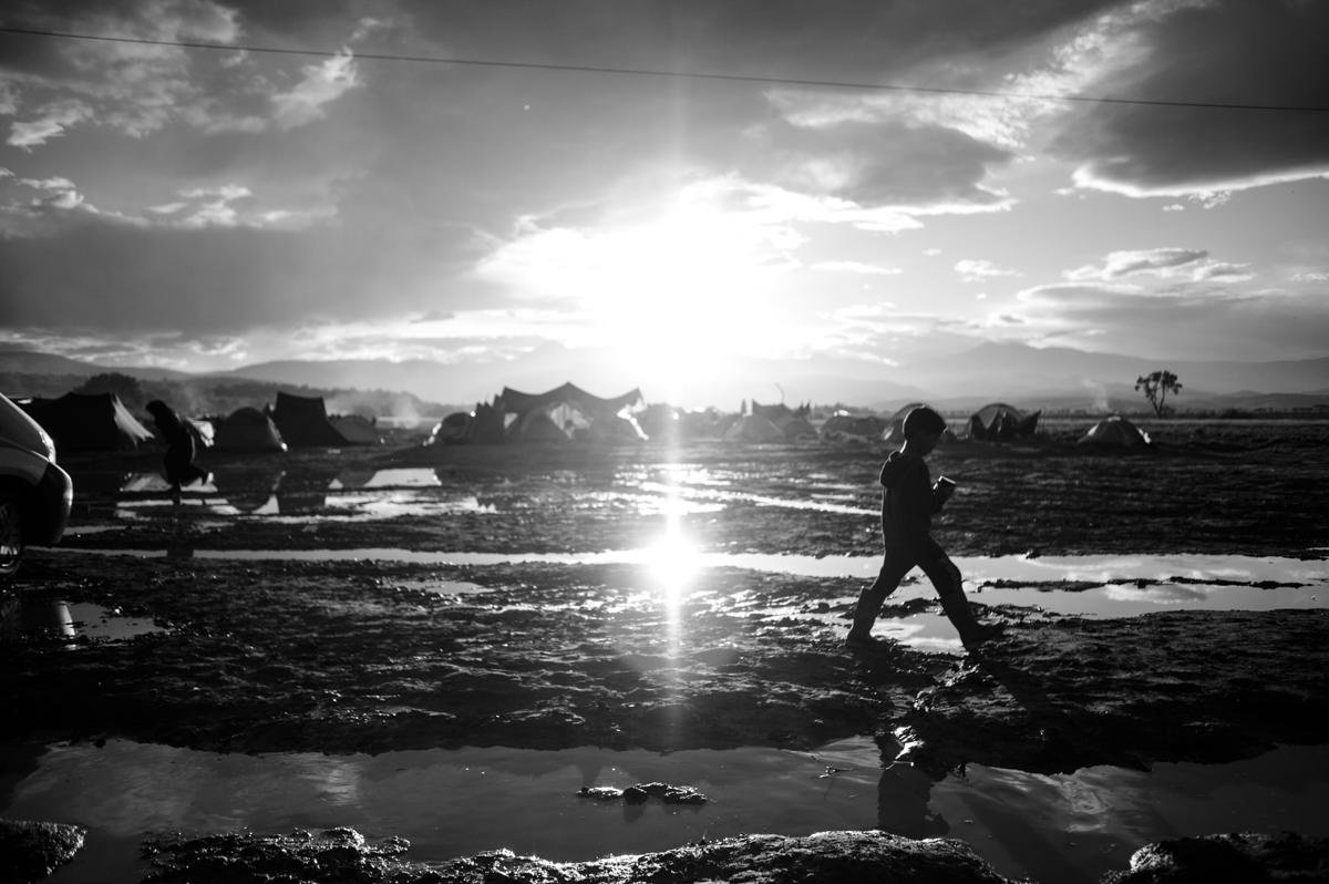 Idomeni - Greece april 2016 - kids going back to his own tent carrying a cup of tea