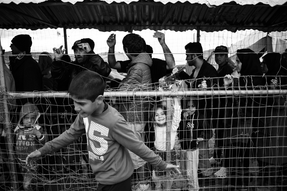 Idomeni - Greece april 2016 - kid passing by the queue for the feeding station