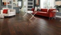 Dark wood floor living room with red and white sofa ...