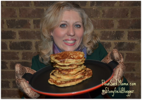 Anne Brock from Flour Sack Mama blog holding stack of homemade pancakes on cast-iron griddle