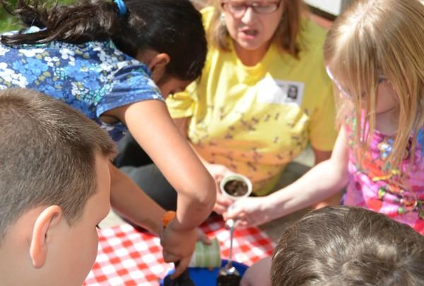 children planting seeds with teacher