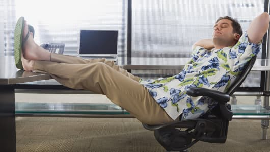 Businessman wearing Hawaiian shirt with feet on desk