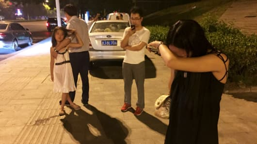 People react near a street after a blast at Binhai new district, in Tianjin municipality, China, August 12, 2015. A huge explosion hit an industrial area in the northeastern Chinese city of Tianjin late on Wednesday evening, triggering a blast wave felt several kilometres away and injuring at least 50 people, domestic media reported.
