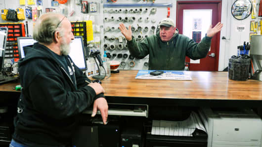 TAN Trucking company owner Ted Nelson talks to J&C Custom Trucking parts manager Gary Bliss about the challenge of running an oil field company during a slowdown in North Dakota.