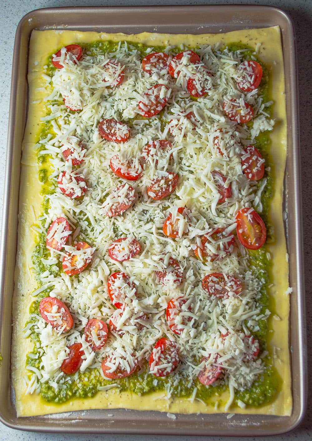 Tomato tart with pesto and mozzarella is topped and ready to go into ...