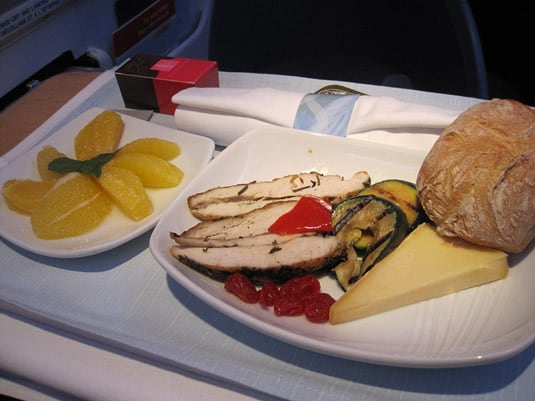 Chilled plate featuring roasted chicken fillets, Edam cheese with grilled zucchini and bell peppers, sun-dried tomatoes. Also served with bread, orange segments and chocolate truffles.