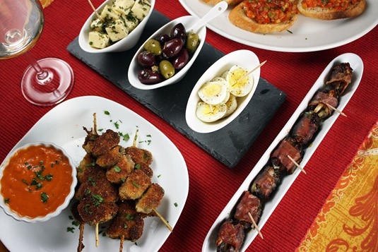 An Assortment of Tapas, Featuring Breaded Mussels Brochettes, Dates Wrapped in Prosciutto, Hard-Boiled Quail Eggs, Marinated Olives and Herbed Cheese