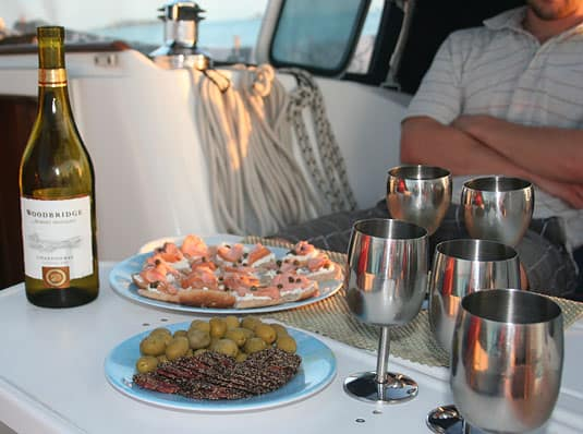 A fancy happy-hour with white wine, black pepper dry sausage, green olives and smoked salmon canapés.