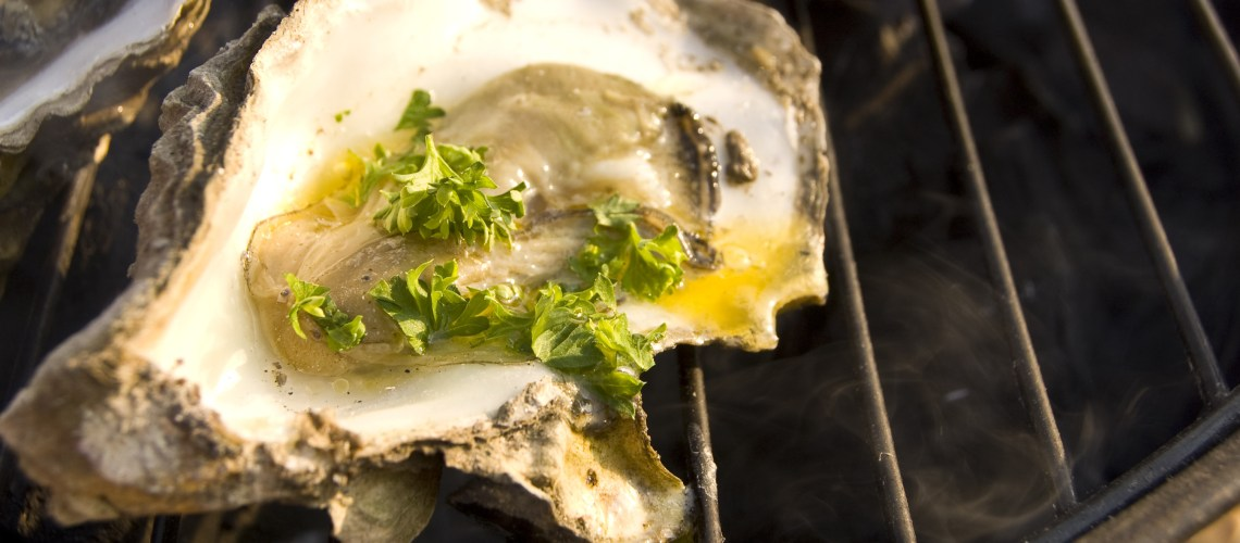 Oyster grilling on barbeque with butter and parsley