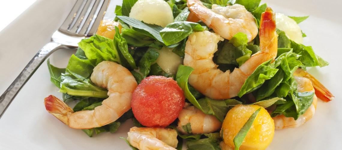 Fancy arrangement of shrimp and melon balls over lettuce.