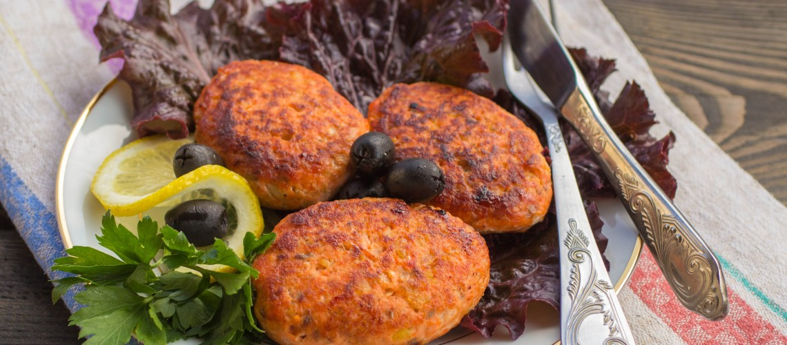 Cutlets of salmon on lettuce leaves with lemon and olives. Selective focus