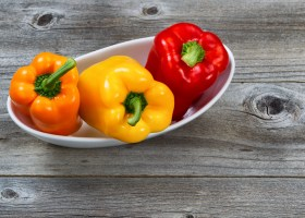 Fresh Bell Peppers in white bowl on rustic wood