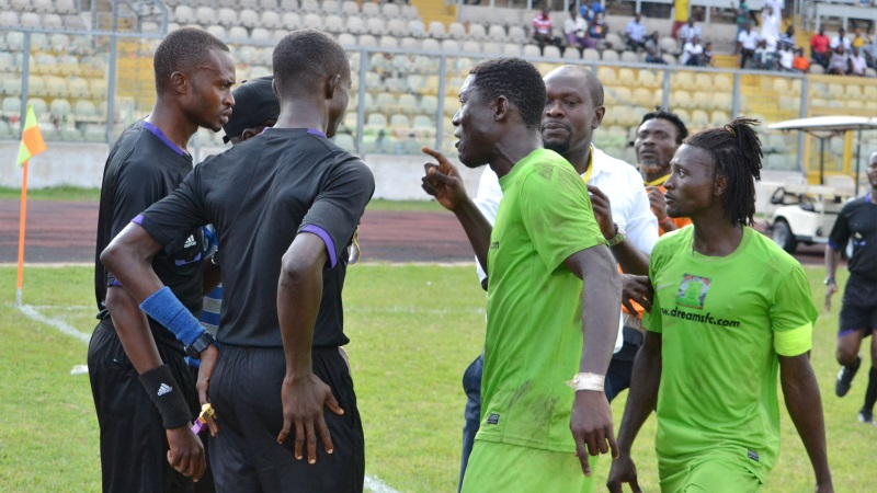 Agitated Dreams FC players charge at referee Nathan Anaafo and assistants after awarding a penalty to Kotoko