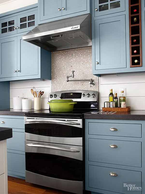 pale blue kitchen cabinets with glass cupboards and marble backsplash