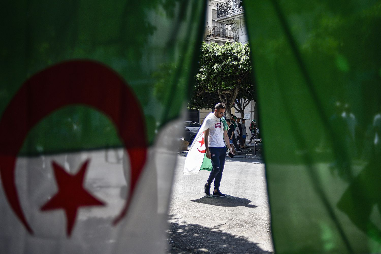 A man draped in an Algerian national flag walks along a street as protesters take part in a demonstration against the ruling class in Algeria's capital, Algiers, on Aug. 23, for the 27th consecutive Friday and marking six months since the movement began.