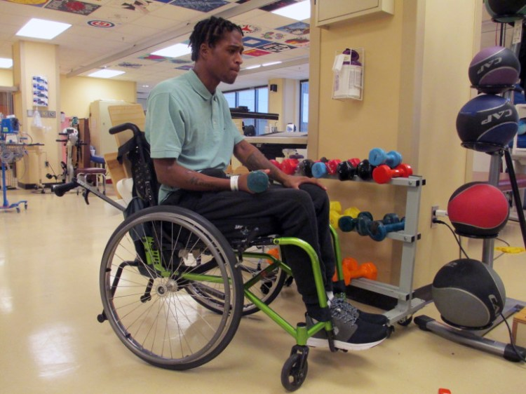 Semaj Clark in physical therapy gym using hand weights.