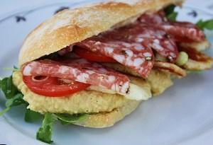 Ciabatta med hummus, stekt halloumi, söta tomater, tunnt skivad salladslök, svartpeppar, olivolja och tunna skivor av en god salami