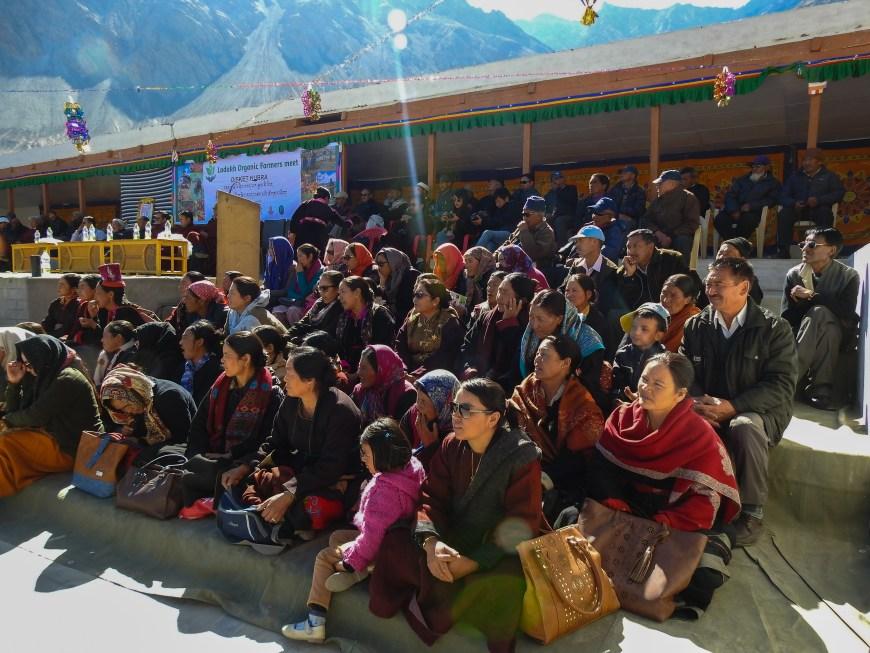 Kvinnor, barn och män som sitter i en trappa längs scenen, där arrangörerna vänt på perspektivet och skapat ett rum där både publiken och talarna på scenen är i fokus