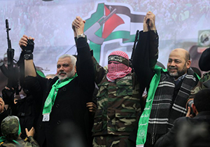 Hamas top leader in the Gaza Strip Ismail Haniya (L), spokesman for the Ezzedine Al-Qassam Brigades, Abu Obaida and Mussa Abu Marzuq (R) greet supporters during a parade marking the 27th anniversary of the Islamist movement's creation on December 14, 2014 in Gaza City. AFP PHOTO / MAHMUD HAMS