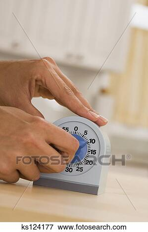 Picture of Woman setting timer for ten minutes ks124177 - Search