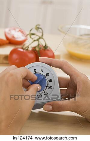Stock Photo of Woman setting timer for ten minutes ks124174 - Search