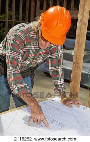 Stock Photo of Hawaii, Senior male construction worker reading