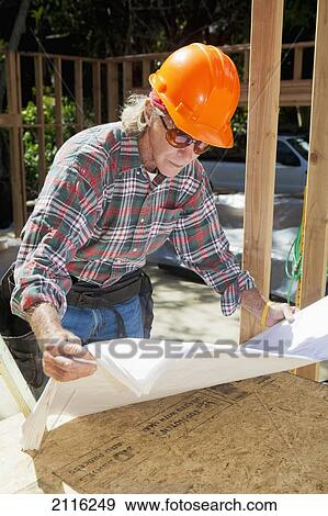 Hawaii, Senior male construction worker reading blueprints at a